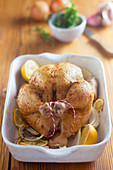 Fried chicken with lemon and onions in a roasting pan