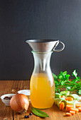 Homemade vegetable stock with a funnel in a glass carafe