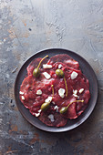Beef carpaccio with parmesan and apple capers (top view)