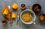 Granolamüsli mit Zimt, Kaki, Ahornsirup, Honig und Nüssen (Aufsicht)