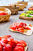 Rows of sliced homegrown tomatoes on wooden plates on burlap tablecloths with woven baskets lined up behind