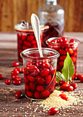 Preserved cornelian cherries in almond liqueur and rum in mason jars