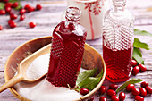 Bottles of homemade cornelian cherry syrup in a wooden bowl with sugar