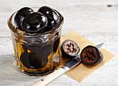 Eingelegte Johannisnüsse (Schwarze Nüsse) im Glas