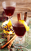 Elderberry and apple punch with orange peel, cloves and cinnamon sticks
