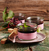 Elderberry panna cotta in glasses with mint, elderflower syrup and wafers