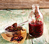 Homemade elderberry herbal syrup with fresh sage and thyme