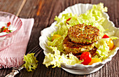 Vegetarian spelt patties on frisee salad