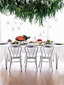 Weihnachtlich gedeckter Tisch mit Schinkenbraten und Beilagen