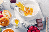 Healthy breakfast with porridge, oatmeal, pancakes, lots of berries and snacks