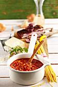 Sauce Amatriciana mit Speck, Käse, Nudeln und Wein auf Tisch