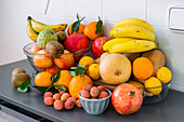 Collection of different fresh tasty ripe tropical fruits in bowls