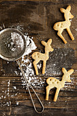 Three Festive Christmas Deer shaped cookie biscuits on a rustic board with icing sugar in a sifter