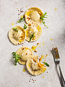 Homemade pumpkin ravioli tortelloni parcels topped with pine nuts, olive oil, rocket and chilli