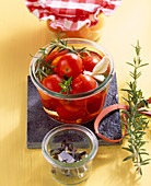 Pickled cherry tomatoes in vinegar with fresh herbs and garlic
