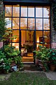 Blick durch Sprossenfensterfront in abendlich beleuchteten Wohnraum