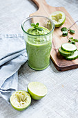 A green smoothie with cucumber and limes