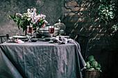 Gedeckter Tisch mit Rotwein, Flieder und Artischocken