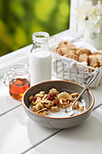 Granola Breakfast Bowl with chocolate cookies and fresh milk near window