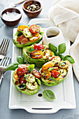 Avocado boats with caprese salad and basil pesto