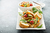 Caprese bruschetta with cherry tomatoes, mozarella and basil pesto