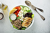 Greek inspired lunch bowl with grilled chicken, quinoa, feta and vegetables