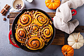 Pumpkin cinnamon rolls in a cast iron pan with nuts and sugar glaze