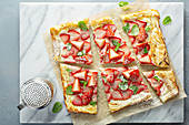 Sweet tart on puff pastry with cream cheese and strawberry