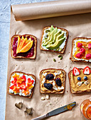 Various savory and sweet toast on baking paper