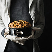 A woman holding a vegan apple cake in a springform pan