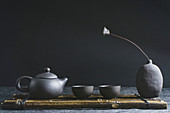 A dark grey tea pot with two tea bowls against a dark background