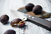 Damsons halved and whole with a knife on a rustic wooden surface