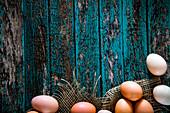 Hühnereier auf blauem Holzuntergrund