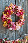 Herbstkranz aus Rosen, Hagebutten und Blättern