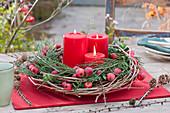 Rote Kerzen in Kranz mit Zieräpfeln