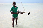 Boy with a toy boat on a beach, Zanzibar
