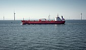 Oil tanker passing offshore windfarm