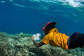 Snorkelling schoolgirl using coral reef ID guide