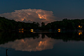 Lightning in clouds reflected in lake