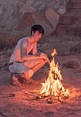 Young man lighting a campfire