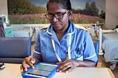 Nurse recording patient care on a tablet computer