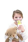 Girl using nebuliser holding teddy bear