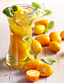 Homemade kumquat vinegar with fresh fruit and lemon balm