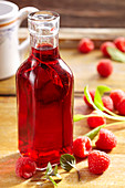 Homemade raspberry vinegar with fresh raspberries, sage, lemon balm, peppermint and white wine vinegar