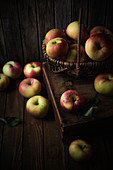 Korb mit Bio-Äpfeln auf Holzuntergrund
