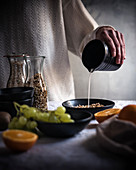 A woman pouring Brazil nut milk into a bowl of muesli