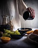 Frau gießt Paranussdrink in eine Schüssel mit Müsli