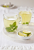 Mint tea in two clear cups on white