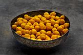 In Kurkuma geröstete Kichererbsen als gesunder Snack im Schälchen