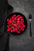 Beetroot gnocchi with sage in a black bowl on a grey surface